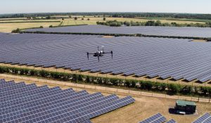 Drone hovering over a solar farm, taken in summer the grass is very dry.