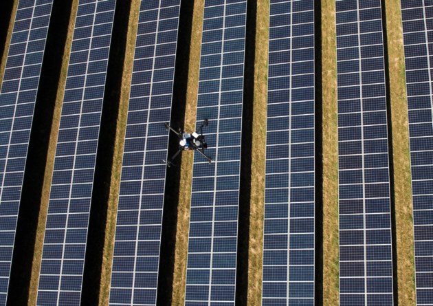 Drone hovering over solar panels